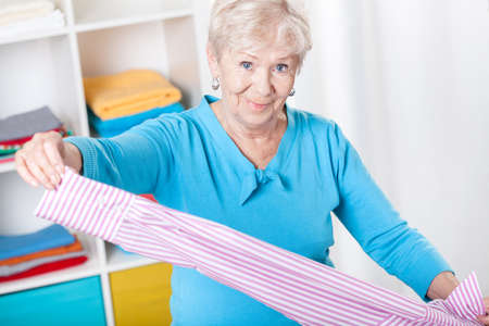 Elderly woman during folding laundry at home photo