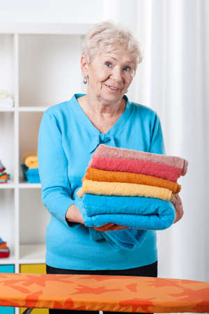 Elderly lady folding towels at her home photo