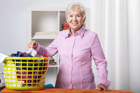 Senior lady wearing shirt during folding laundry photo