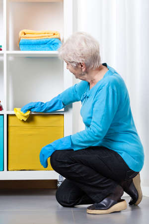 Elderly woman during dusting furniture at home photo