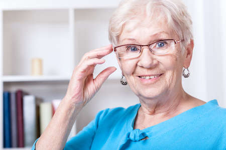 Smiling grandmother wearing reading glasses at home photo