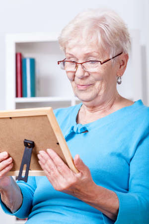 Elderly lady wearing glasses viewing family picture photo