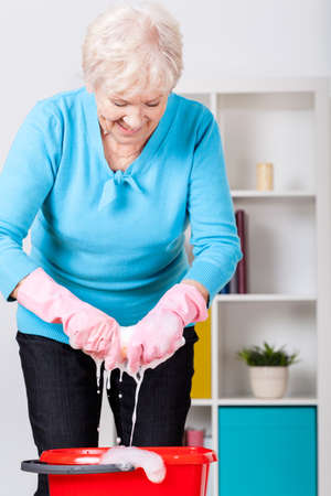 Elderly lady wringing the cloth at home photo