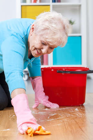 Senior woman during washing floor at home photo