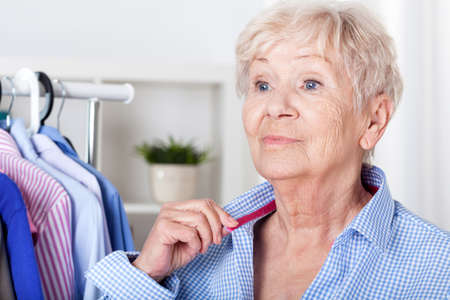 Senior lady during wearing shirt in wardrobe photo
