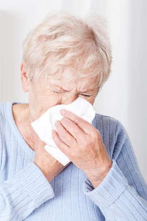 gripe: Se�ora mayor con la ejecuci�n de la nariz en el hogar Foto de archivo