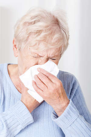 catarrh: Senior lady with running nose at home