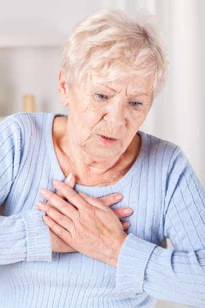 dolor de pecho: Señora mayor con un fuerte dolor en el pecho, vertical Foto de archivo