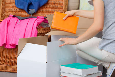 apartment cleaning: A woman packing colorful books into a cradboard box