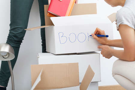 moving out: Woman descripting white boxes before moving out