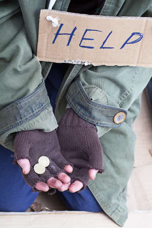 Beggar hands with coins asking for a help photo