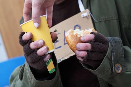 Women giving hot tea to poor homeless man photo