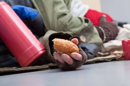 Poor man with piece of bread sleeping on a street Stock Photo - 26312872