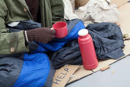Beggar warming himself by a hot tea  Stock Photo