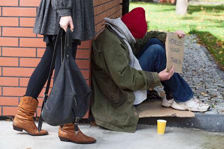 limosna: Mujer que pasa por las personas sin hogar hambriento necesitados