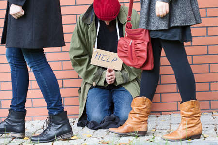 People in rush passing by the homeless man in need photo