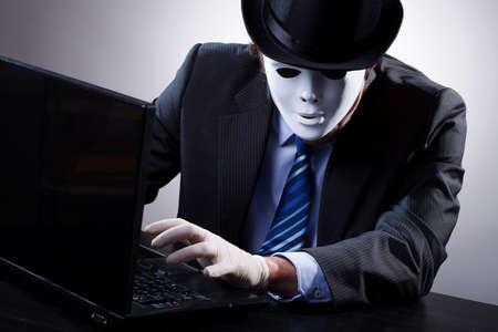 ハッカー スーツとコンピューターの前にマスクを身に着けています。 写真素材