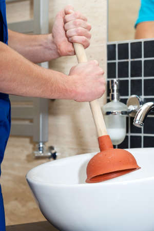 unblock: Plumber unblocking the white sink with tool