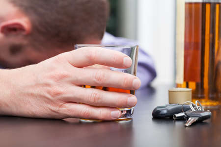 sad man alone: Driver sleeping on table with glass with an alcohol
