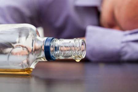 botellas vacias: Drunk hombre durmiendo con una botella casi vacía de alcohol