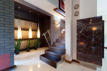 banister: Corridor with metal and wooden stairs in modern interior Stock Photo