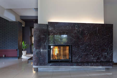 A black brick wall with a small and stylish fireplace Stock Photo - 26388750