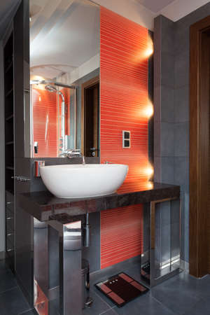 A bathroom sink by a wall with orange tiles Stock Photo - 26388751