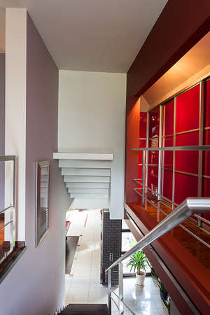 Stairs with a metal banister, red wall Stock Photo - 26388798