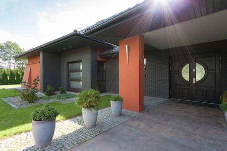 Una puerta de entrada de una casa de color negro con detalles cobrizos