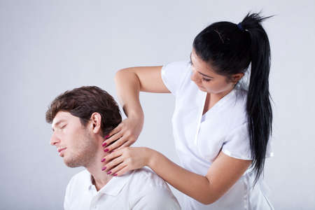 A masseuse taking care of her patients neck