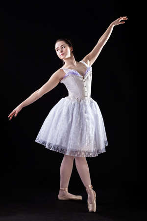 A graceful ballet dancer in a pose wearing a white dress