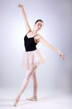A posing ballet dancer wearing a tulle cream skirt Stock Photo