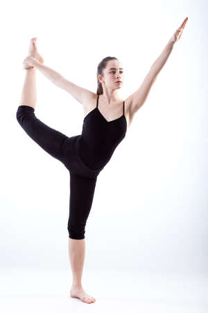demanding: A gymnast in black stretching her leg in a demanding pose Stock Photo
