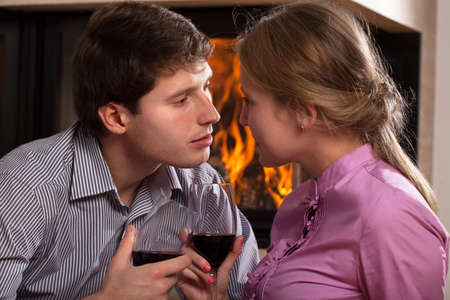 proposing a toast: A couple proposing a toast by a fireplace