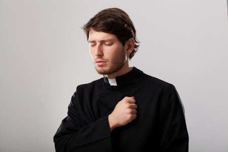 Young christian priest is regretting for sins Stock Photo