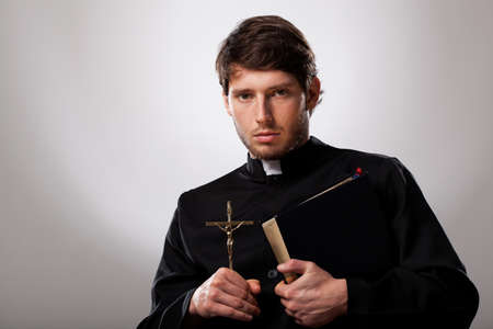 Young priest is holding a cross and holy bible