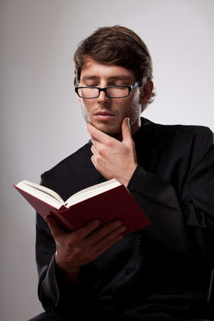 Young christian priest in glasses is reading