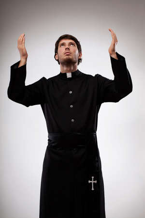 Young christian priest is raising hands and praying