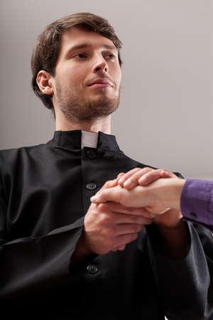 toog: Jonge christelijke priester houdt gelovige kant Stockfoto