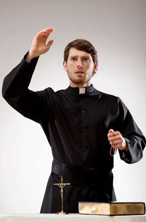 Young priest is preaching a sermon and holding a rosary Stock Photo
