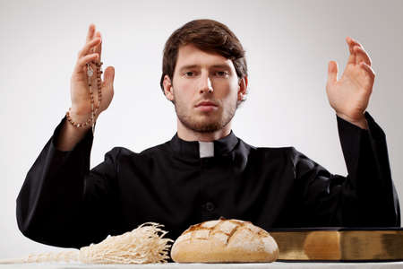 Young priest with rosary bread sprinkler and Holy Bible Stock Photo