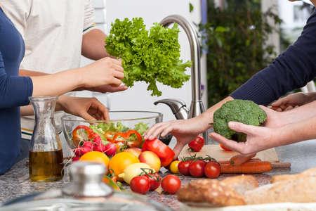 Vrienden samen koken de veagetarian diner in de keuken