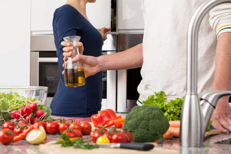 Wife gives husband olive oil to prepare healthy dinner at home photo