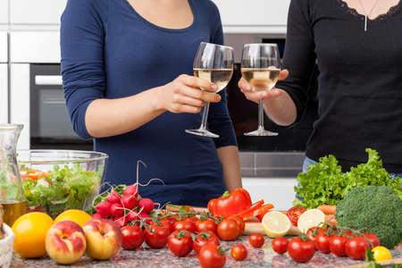 lesbianas: Pareja de lesbianas que prepara la cena y bebiendo vino en casa