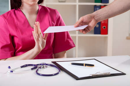 Doctor expressing disapproval for bribe at work photo