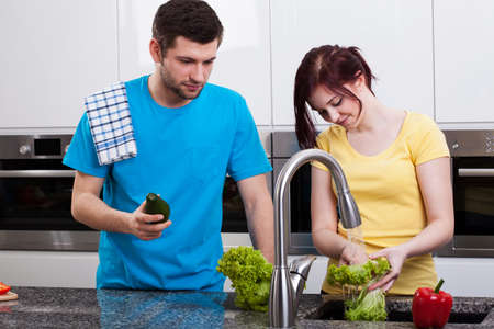 Wife washing broccoli in kitchen sink and her husband photo