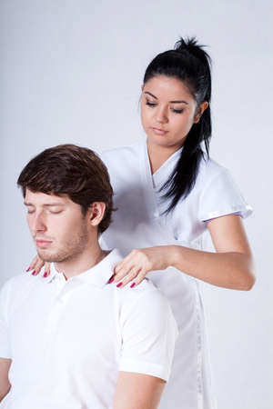 A female specialist massaging handsome clients shoulders