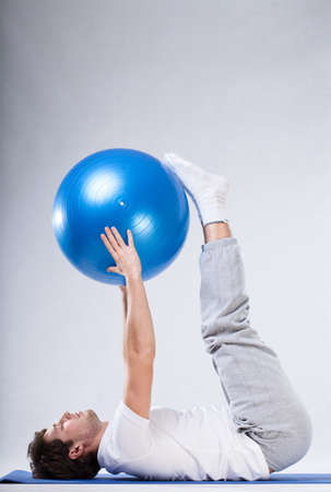 pilates man: A man doing pilates exercises with a big blue rubber ball Stock Photo