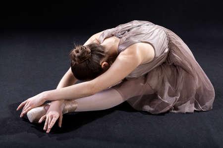 A ballerina bending forward while practising in an elegant costume