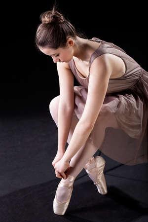 An elegant ballet dancer tying her pointe shoes